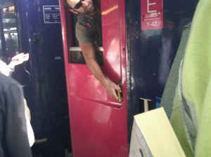 man opening a British train door by reaching through a window